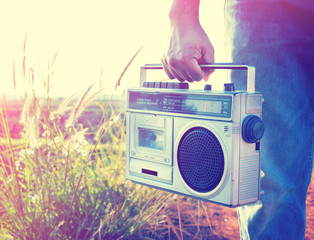 Man hand holding vintage radio on nature background