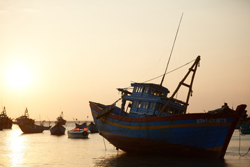fishing boats in the sea at sunset