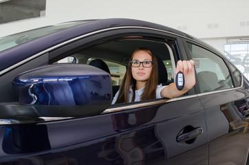 Девушка сидит в новом автомобиле и показывает ключи от него