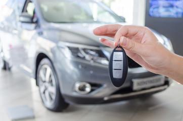 Демонстрация ключей от нового автомобиля на фоне автомобиля