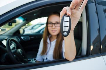 Молодая девушка сидит в новом автомобиле и показывает ключи от него