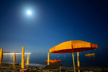 parasols by the sea under a bright moon