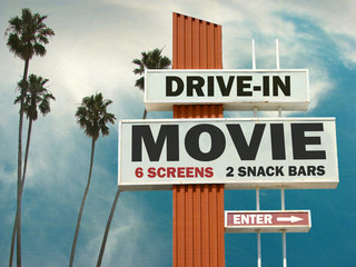aged and worn vintage photo of drive in movie sign with palm trees
