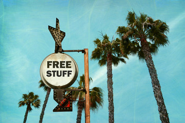 aged and worn vintage photo of free sign with palm trees