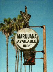 aged and worn vintage photo of marijuana sign with palm trees