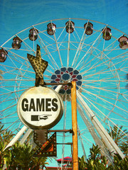 aged and worn vintage photo of games sign with ferris wheel