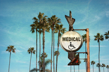 aged and worn vintage photo of medical sign with palm trees