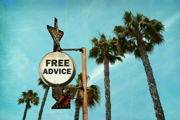 aged and worn vintage photo of free advice sign with palm trees