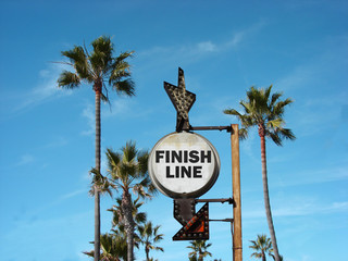 aged and worn vintage photo of finish line sign on beach