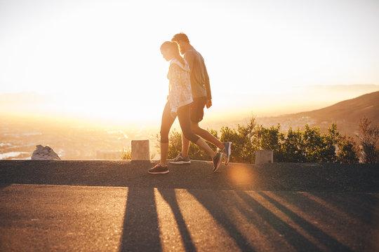Couple walk along road at sunrise