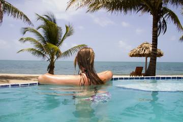 Woman swimming in infinity pool beside ocean