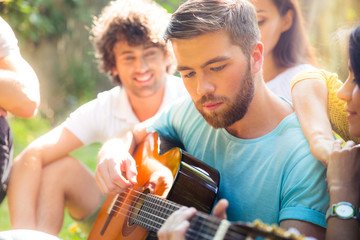 Students with guitar resting outdoors