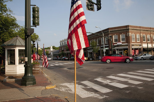 American Flags with red car driving in front of storefronts of Lexington, MA on Memorial Day, 2011