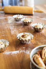 Unbaked cinnamon rolls in small baking forms. Selective focus