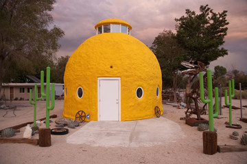 Roadside attraction shows campy objects in front of Yellow domed house, along Route 395, California.
