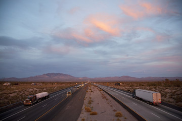 Cars drive Interstate 15 at sunset at California Nevada border looking east.