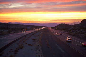Cars drive Interstate 15 at sunset at California Nevada border looking west.