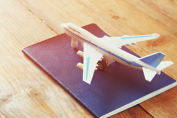 toy airplane and passport over wooden table. retro style image