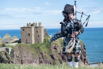 Traditional scottish bagpiper in full dress code at Dunnottar Castle in Stonehaven Wall mural