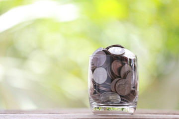 silver coin in glass is placed on a wood floor with colorful bok