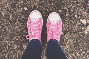 Pink polka pot trainers and woman legs in jeans