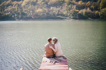 Happy couple sitting on a wooden bridge near lake