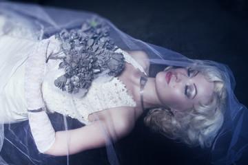 Sleeping Beauty. Beautiful lifeless bride in white dress lying o