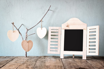 decorative chalkboard frame and wooden hanging hearts over wooden table. ready for text or mockup. retro filtered image