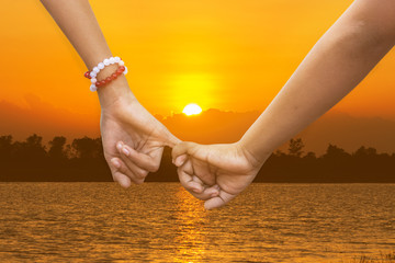 child girl couple in love holding hands river sunset background
