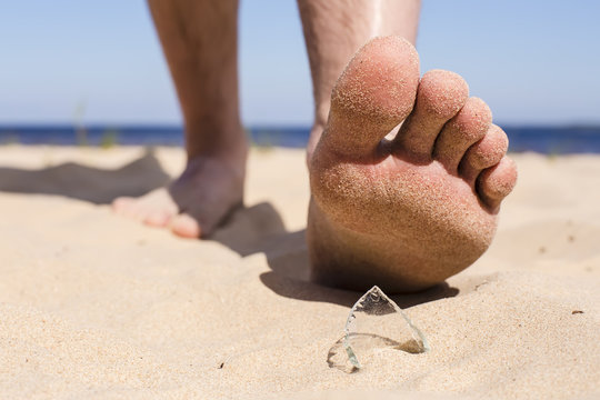 Man goes on the beach and the risk of stepping on a splinter of broken bottle glass, which is lying on the sand littered in places with poor environmental conditions