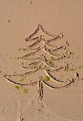 Christmas tree drawing on beach sand