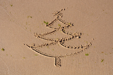 Christmas tree drawing on beach sand