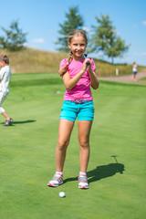 Cute little girl playing golf on a field outdoor. Summertime