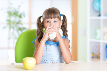 Smiling child girl drinking milk from glass at home
