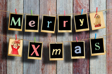 Merry christmas words hanging on clothesline on wood background.