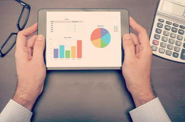 Businessman checking statistics on tablet device