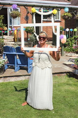 An english lady wearing a beautiful dress and holding an open picture frame in an english garden