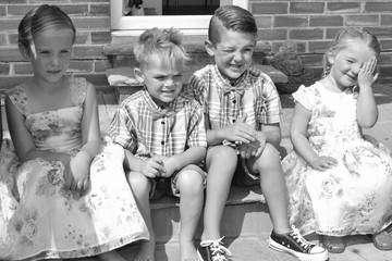 A group of four children sitting on a step
