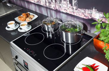 Stainless steel induction cooker in modern kitchen.