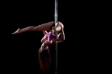Junge Frau macht Pole Dance an der Stange
