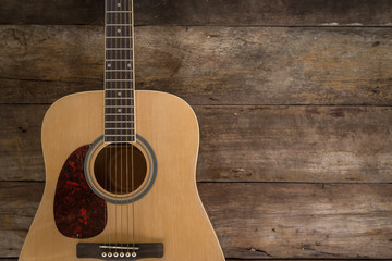 Top view of guitar on dark wood floor texture in darken tone