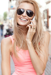 Happy blonde woman talking by mobile phone.