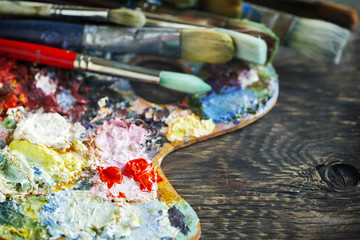 Artist paint brushes and palette on wooden background. Selective focus