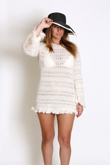 Young Attractive Female Model wearing White Macrame Dress and Black Wide Brim hat.