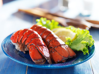 two lobster tails on blue plate with garnish for dinner