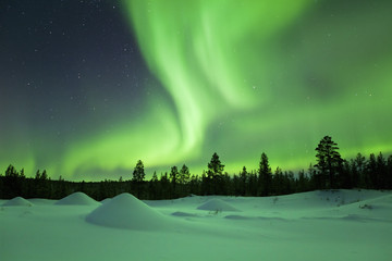 Aurora borealis over snowy winter landscape, Finnish Lapland