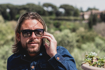 Casual man with long blonde hair and sunglasses calling with mob