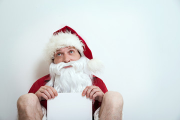 Jobless half naked Santa sit with blank table and looks like beggar
