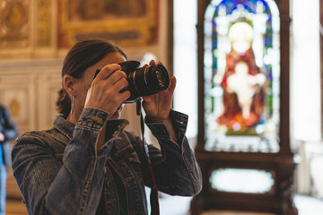Female brunette tourist photographing interior of church.
