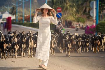 blonde girl in Vietnamese dress watches goats flock